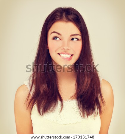 Beauty portrait of a young brunette woman  biting her lips.  - stock photo
