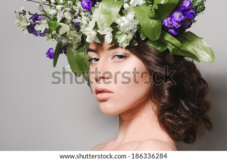 Beauty portrait of a young girl with flowers in her hair on gray studio background