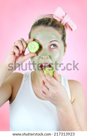 Beauty portrait of a young happy woman wearing a pink headband, white tank top and a green facial mask is holding a slice of cucumber in front of her left eye and is about to eat the second slice.