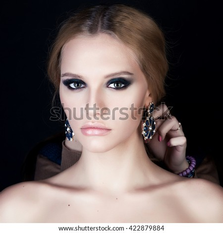 Beauty portrait of a young naked blonde girl with a tail. Smokey eyes and big earrings. Hand on chest