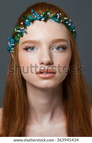 Beauty portrait of a young redhead woman with hoop on her head looking at camera  - stock photo