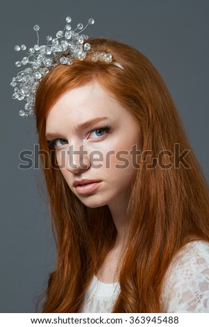 Beauty portrait of a young redhead woman with hoop on her head looking at camera over gray background - stock photo