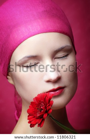 beauty portrait of a young woman in pink with a gerbera flower - stock photo