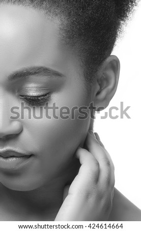 Beauty portrait of African woman with perfect skin looking down. Isolated on white background. Black and white