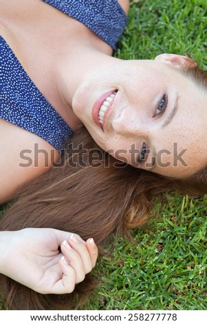 Beauty portrait of an attractive joyful young beautiful tourist woman laying down on green grass in a park, relaxing on a summer holiday, smiling. Healthy living well being lifestyle, exterior. - stock photo