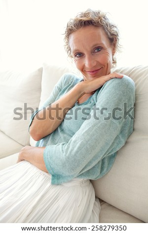 Beauty portrait of an attractive mature caucasian woman sitting on a white sofa at home, relaxing on a sunny day, indoors lifestyle. Health, wellness and well being. Skin care and beauty. - stock photo
