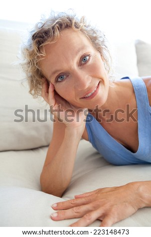 Beauty portrait of an attractive middle aged healthy woman relaxing on a white sofa at home, laying down relaxing and smiling. Interior home living and well being lifestyle.