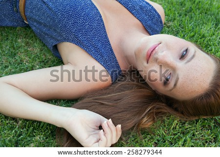 Beauty portrait of an attractive young beautiful tourist woman laying down on green grass in a park, relaxing on a summer holiday, smiling. Healthy living, beauty and well being lifestyle, exterior. - stock photo