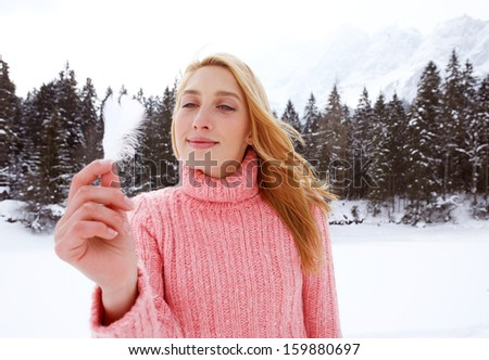 Beauty portrait of an attractive young woman in the snow mountains landscape on vacation, holding a natural soft white feather in her hand and smiling during a cold winter day, outdoors.