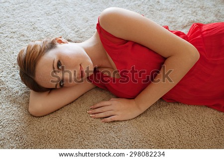 Beauty portrait of an attractive young woman laying on a bed at home wearing a bright red dress and gently smiling and looking at camera, home bedroom interior. Beauty feminine indoors lifestyle. - stock photo