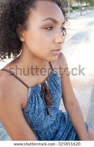 Beauty portrait of and elegant and stylish african american black teenager girl sitting relaxing, looking ahead, being moody outdoors. Young bohemian woman lifestyle. Aspirational living, exterior. - stock photo