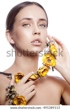 Beauty portrait of attractive caucasian young girl with natural make-up and yellow flowers necklace looking at camera. Studio shot Isolated on white background.