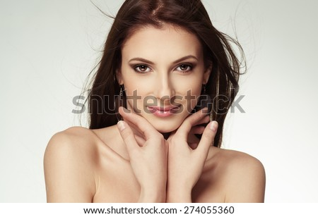 Beauty portrait of attractive female touching her face. Skin care, cosmetics and makeup concept.  - stock photo