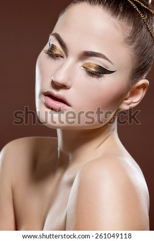 Beauty portrait of attractive model face with bright visage. Gold eye makeup and soft beige lips make-up. Gold arrow make up - stock photo