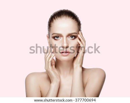 Beauty portrait of attractive model with blue eyes and brunette hair. Fresh, clean skin.  Professional makeup. Tender colors. Pink background not isolated. - stock photo