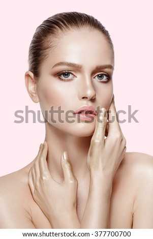 Beauty portrait of attractive model with blue eyes and brunette hair. Fresh, clean skin.  Professional makeup. Gold hands. Tender colors. Pink background not isolated. - stock photo