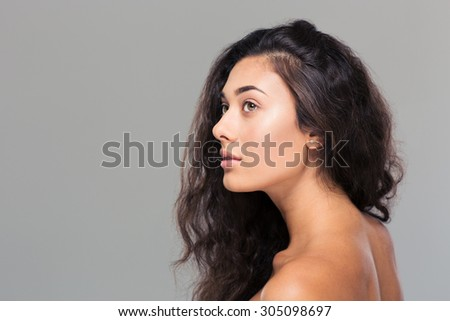 Beauty portrait of attractive woman looking away over gray background