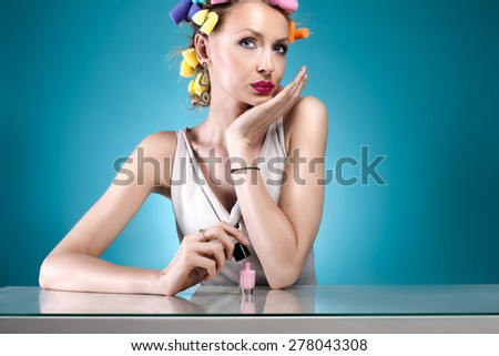 Beauty portrait of attractive woman posing with nail polish and with curlers on her head. Blue background. - stock photo