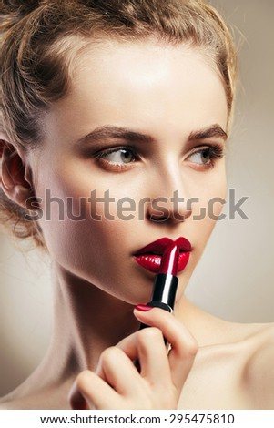 Beauty portrait of attractive woman with fashion red lips makeup. Applying lipstick. Sexy open female mouth. Perfect skin. - stock photo