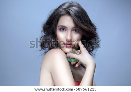 beauty portrait of attractive young caucasian woman brunette on blue background studio shot applying perfume face skin makeup looking at camera