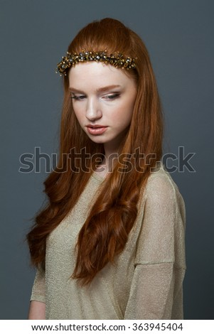 Beauty portrait of attractive young redhead woman with hoop on her head over grey background