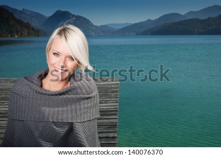 Beauty portrait of beautiful adult short-haired blond woman posing in a pontoon near a lake by evening and wearing a grey sweater - stock photo