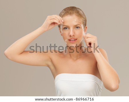 beauty portrait of beautiful blonde woman peeling off a facial mask, smiling - stock photo
