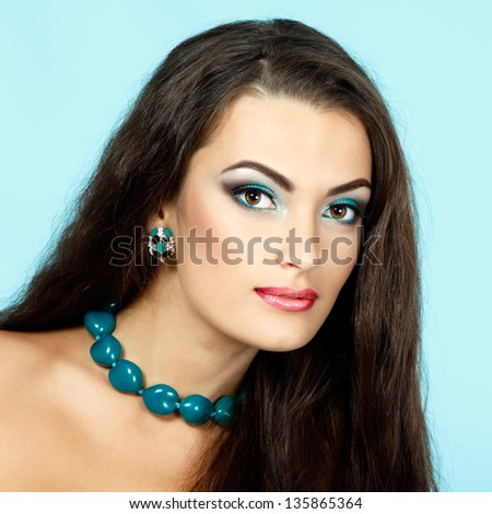 Beauty portrait of beautiful young fresh woman with long brown healthy hair. Over blue background - stock photo