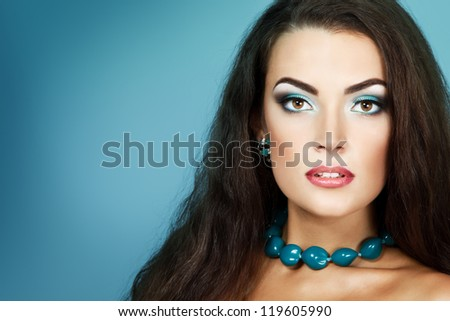 Beauty portrait of beautiful young fresh woman with long brown healthy hair. Over turquoise background - stock photo