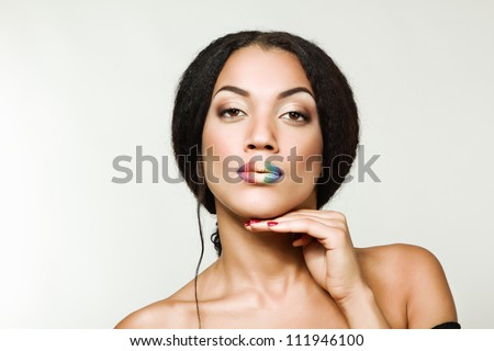 Beauty portrait of beautiful young mulatto fresh woman with rainbow lipstick, face and shoulders closeup - stock photo