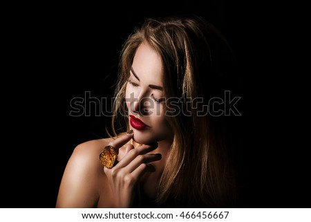 Beauty portrait of blond girl with jewelry on black background