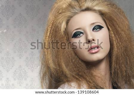 beauty portrait of  blonde girl with dark glossy make-up and voluminous rock hair-style on gray background