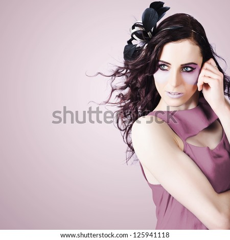 Beauty Portrait Of Bright Cosmetic Girl With Wavy Brunette Hair Style, Fascinator And Creative Purple Makeup - stock photo