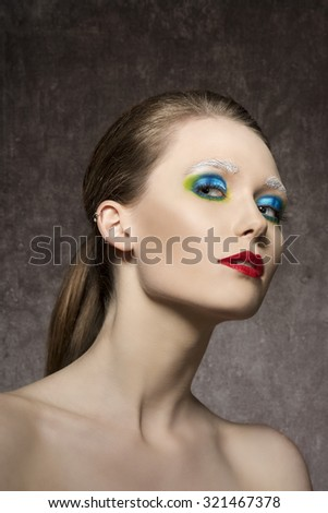 beauty portrait of charming young woman with creative artistic colorful make-up and red lipstick, charming expression  - stock photo