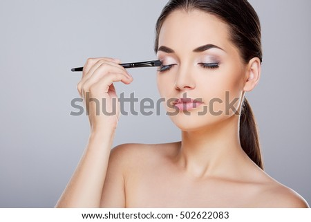Beauty portrait of girl with perfect nude make-up. Painting eyelids with eye shadows. Closed eyes. Beauty salon. Head and shoulders, studio, indoors