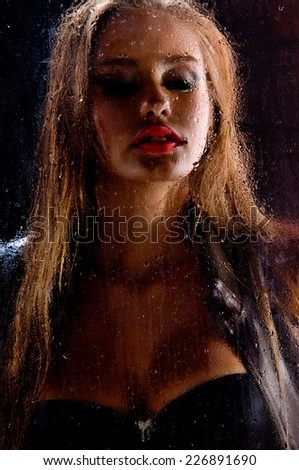 Beauty portrait of gorgeous woman behind rainy glass - stock photo