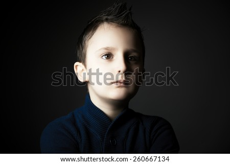 Beauty portrait of handsome kid against dark grey background - stock photo