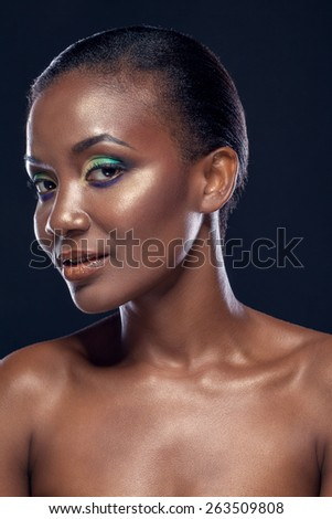 Beauty portrait of handsome smiling ethnic african girl, on dark background - stock photo