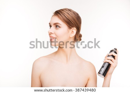 Beauty portrait of happy young woman applying hairspray on her hair over white background - stock photo