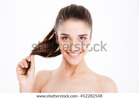 Beauty portrait of happy young woman touching her hair over white background - stock photo