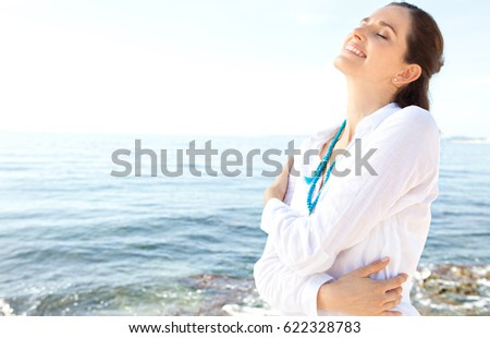 Beauty portrait of healthy mature woman hugging herself feeling free and joyful, leaning head back in nature coast by sea, wellness, sunny outdoors. Well being, freedom breathing, relaxing lifestyle.