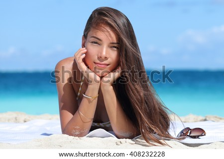 Beauty portrait of mixed race Asian Caucasian woman on beach. Young lady with perfect skin wearing bikini and jewelry - bracelet and necklace - relaxing on beach. Fashion model on vacation travel.