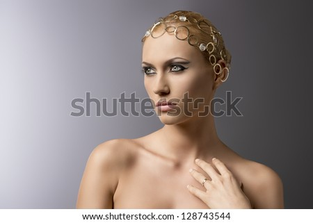 beauty portrait of pretty blonde girl with gold jewellery on the head, cute make-up and naked shoulders - stock photo