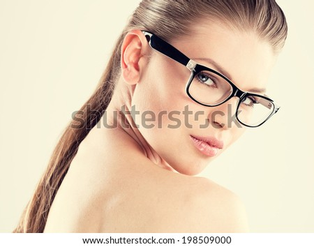 Beauty portrait of pretty girl wearing stylish eyeglasses. Young attractive glamour Caucasian woman with naked shoulders posing in studio.   - stock photo