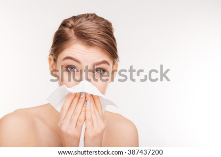 Beauty portrait of pretty woman blowing nose and using paper handkerchief over white background