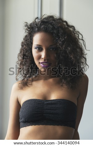 Beauty portrait of pretty young mulatto woman with beautiful makeup and curly hair. She is sensual