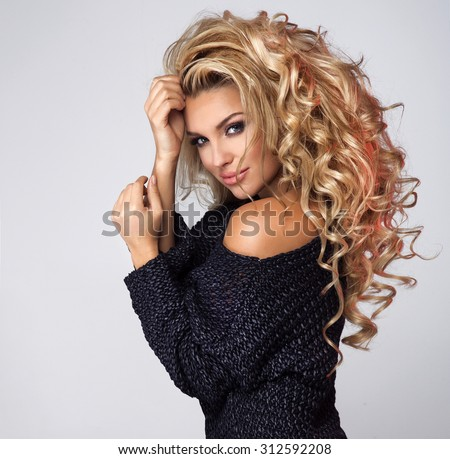 Beauty portrait of romantic blonde woman with long curly hair. Girl wearing fashionable navy blue sweater. Studio shot.  - stock photo