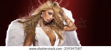 Beauty portrait of sensual blonde woman with long healthy hair.Girl posing with angel wings