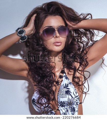 Beauty portrait of sensual brunette woman wearing sunglasses - stock photo