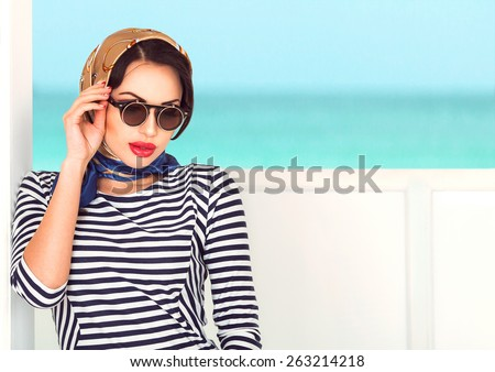 Beauty portrait of sexy smiling brunette woman with red plump lips and trendy sun glasses with colorful scarf on her head relaxing on the yacht. Cruise summer fashion. Ocean background with copy space - stock photo